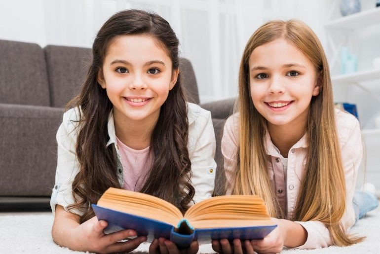 two girls on the floor reading in a book - decoding instead of vocab cramming